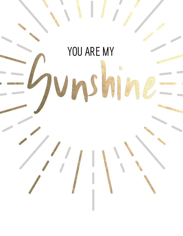 """White greeting card with the words, """"YOU ARE MY SUNSHINE"""" within a round sunburst in black, silver and gold foil."""